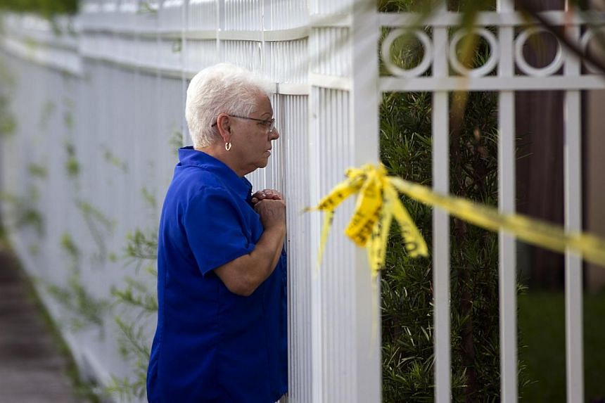 An unidentified woman looks through a fence near a murder scene, on Aug 8, 2013. A man is being held in the United States after apparently gunning down his wife and posting a gruesome picture of her dead body on Facebook, authorities said on Thursday