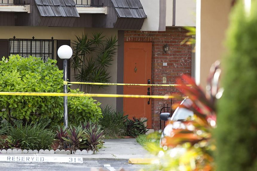 Police tape blocks the entrance to a murder scene in Miami, on Aug 8, 2013. A man is being held in the United States after apparently gunning down his wife and posting a gruesome picture of her dead body on Facebook, authorities said on Thursday. --
