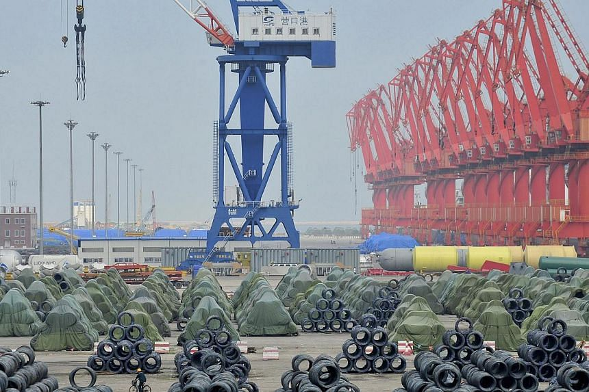 A worker rides his bicycle past piles of steel coils for export at a port in Yingkou, Liaoning province on Aug 9, 2013.China's industrial production growth accelerated in July to a five-month high of 9.7 per cent year-on-year, the government an
