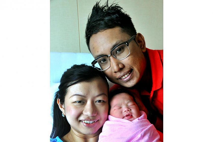 Engineer Ahmad Mahmood, 28, and his wife, teacher Nur Irdina, 27, with their daughter Naila Irdina. Naila was the first baby girl born on National Day in 2011, after she was delivered at midnight at Raffles Hospital on Aug 9, 2011. -- FILE PHOTO: SHI