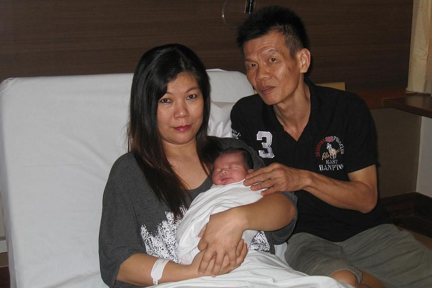 Mr Toh Ho Beng, 41, and his wife, Madam Tan Bee Geok, 39, with their son Augustine, who was born just seconds after midnight at Mt Alvernia Hospital on Aug 9, 2011. -- MY PAPER FILE PHOTO: LOW MINMIN