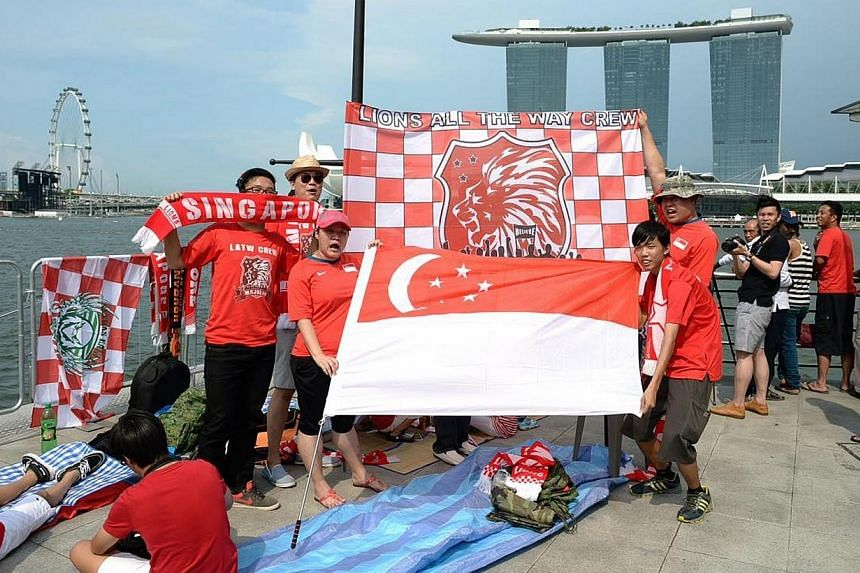 (From left) Eric Teo, 15, Hwee Heng, 38, Eileen Siaw, 34, Henry Han, 37, and Ching Yan, 18, pose for the camera with their flags on Friday, Aug 9, 2013. Early birds hoping to catch a glimpse of this year's National Day Parade camped out in front of t