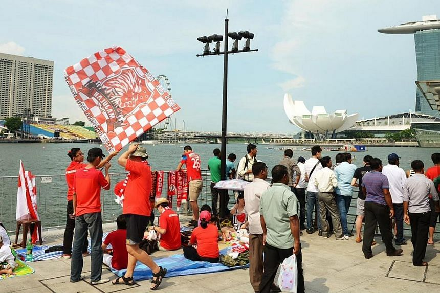 Early birds hoping to catch a glimpse of this year's National Day Parade camped out in front of the Merlion on Friday.-- ST PHOTO: DESMOND WEE