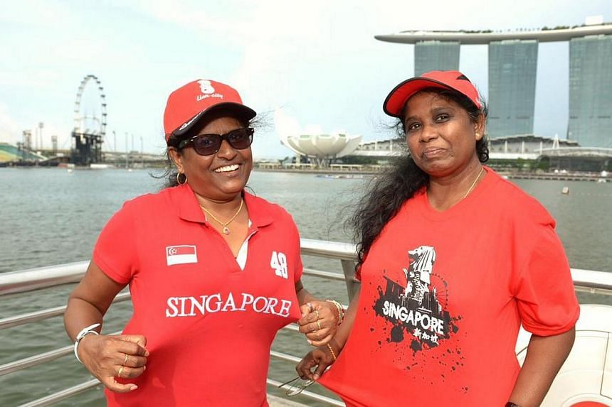 (From left) Ms Ajantha Sadamali, 48, and Ms Kalyani Renuka Ranaweera, 52, pose for the camera on Friday, Aug 9, 2013. Early birds hoping to catch a glimpse of this year's National Day Parade camped out in front of the Merlion on Friday. -- ST PHOTO: