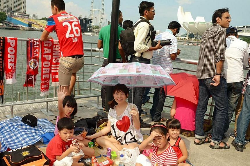 (From left) Benjamin Liew, 4, Clarah Tan, 8, Ms Lim Chin Fern, 33, Cherisse Tan, 4, and Kara Liew, 8, enjoy their spot on Friday, Aug 9, 2013. Early birds hoping to catch a glimpse of this year's National Day Parade camped out in front of the Merlion