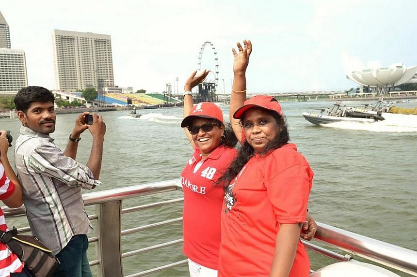 (From left) Ms Ajantha Sadamali, 48, and Ms Kalyani Renuka Ranaweera, 52, pose for the camera on Friday, Aug 9, 2013. Early birds hoping to catch a glimpse of this year's National Day Parade camped out in front of the Merlion on Friday.-- ST PH