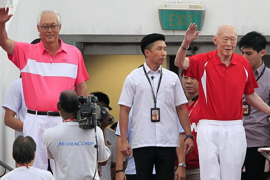 Emeritus Senior Minister Goh Chok Tong (left) and former Prime Minister Lee Kuan Yew (right) wave to the crowd as they arrive at the National Day Parade 2013 at the floating platform on Friday, Aug 9, 2013. -- ST PHOTO: KEVIN LIM