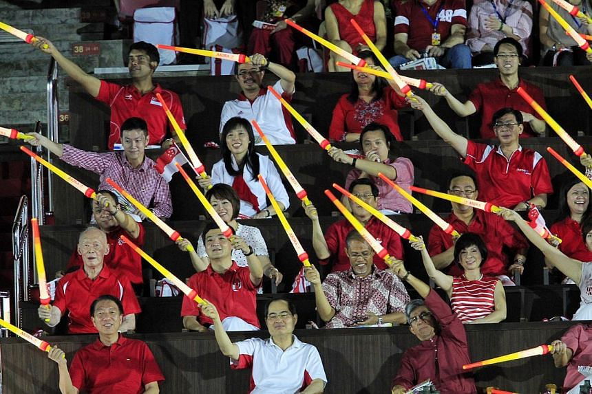 Former Prime Minister Lee Kuan Yew (seated second row, first from left)joins in the fun with the other ministers and MPs in waving their light sticks.--ST PHOTO: KEVIN LIM