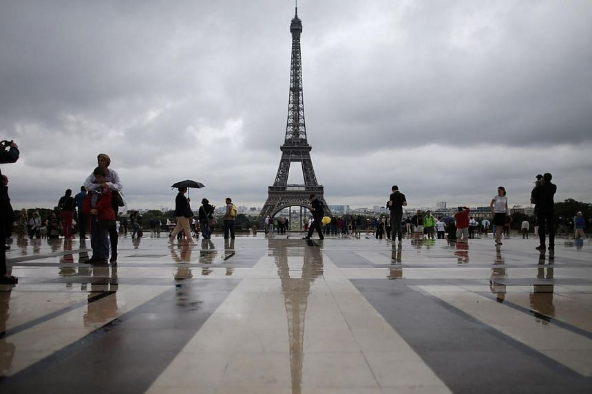 Tourists stroll on the Trocadero square, in front of the Eiffel Tower in Paris on Wednesday, Aug 7, 2013. The Eiffel Tower was completely evacuated on Friday afternoon following a bomb alert, a police official told Reuters.-- FILE PHOTO: REUTER