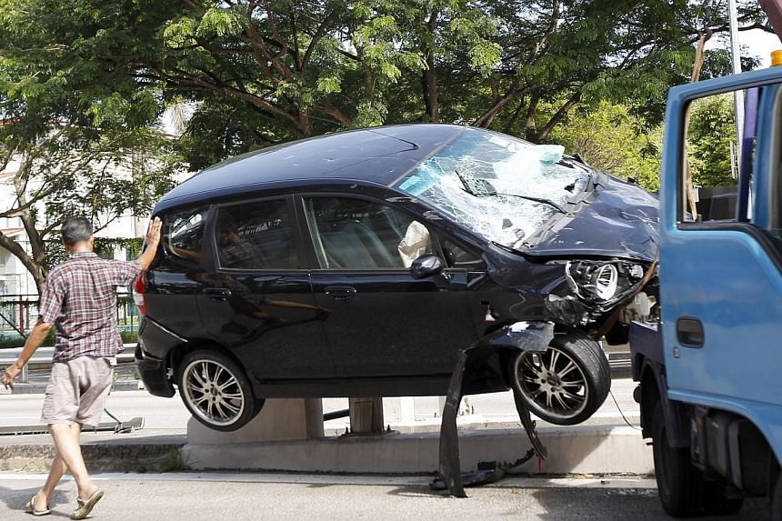 A Honda Jazz rammed into the barrier at the centre of Farrer Road and flipped right on top of it on Friday morning.-- ST PHOTO:WONG KWAI CHOW