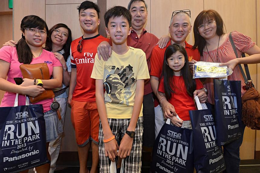 Profile picture of Chew Chow Cher (second from right), 45, and Tan Ah Khong (third from right), 56, with their family after collecting their race packs. Some 200 participants of the ST Run in the Park collected their race packs yesterday for the Augu