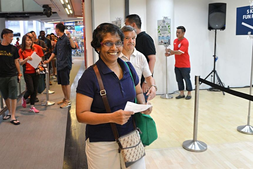 Pushpa Winter, 52, was first in line to collect her race pack. Some 200 participants of The Straits Times' Run in the Park collected their race packs yesterday for the August 25 race, and were in line before collection started officially at 11am. --