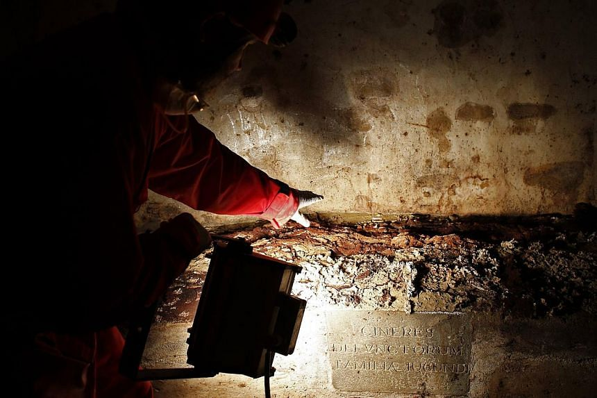 A researcher shows remains inside a tomb opened in the stone church floor above the family crypt of Florentine silk merchant Francesco del Giocondo in the Santissima Annunziata basilica in Florence on Aug 9, 2013.Researchers opened a cent