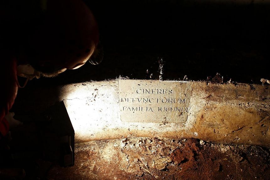 A researcher shines a light on a tomb opened in the stone church floor above the family crypt of Florentine silk merchant Francesco del Giocondo at the Santissima Annunziata basilica in Florence on Aug 9, 2013.Researchers opened a centuri