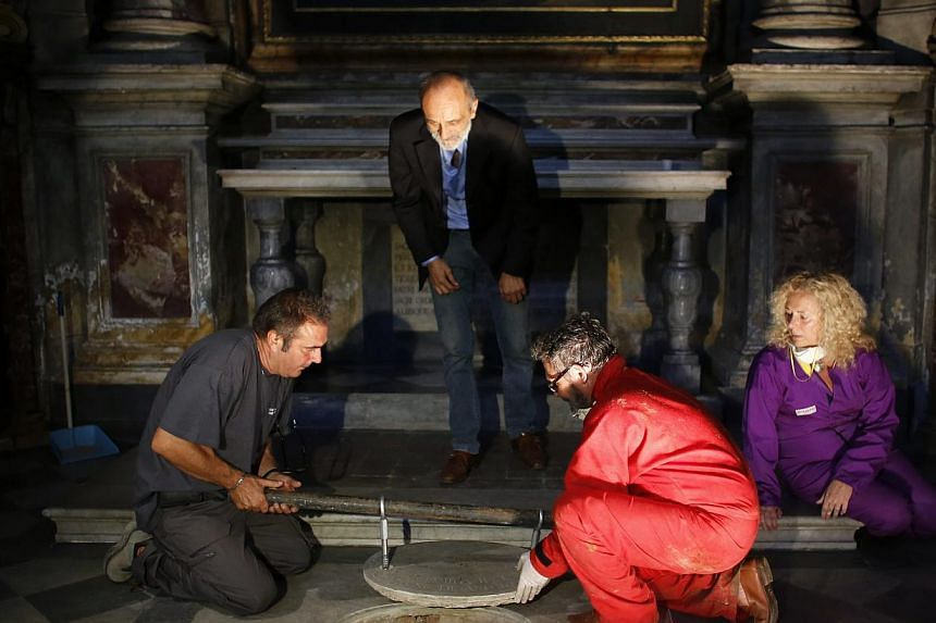 Silvano Vinceti (top), head of Italy's National Committee for the Promotion of Historic and Cultural Heritage, looks on as researchers open the tomb in the stone church floor above the family crypt of Florentine silk merchant Francesco del Giocondo a
