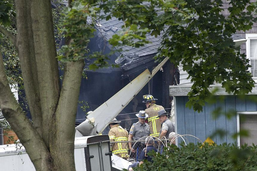 Emergency personnel survey the damage at the site of a plane crash in East Haven, Connecticut, on Aug 9, 2013.United States rescue workers scrambled on Friday to find two children missing and feared dead after a twin-engine aircraft crashed int