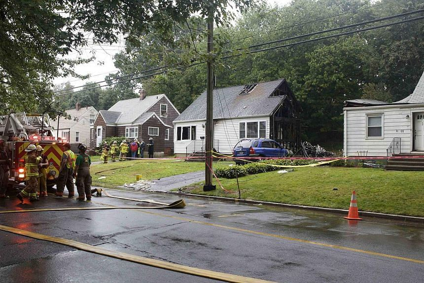 Burnt and damaged homes are pictured at the site of a plane crash in East Haven, Connecticut, on Aug 9, 2013. United States rescue workers scrambled on Friday to find two children missing and feared dead after a twin-engine aircraft crash