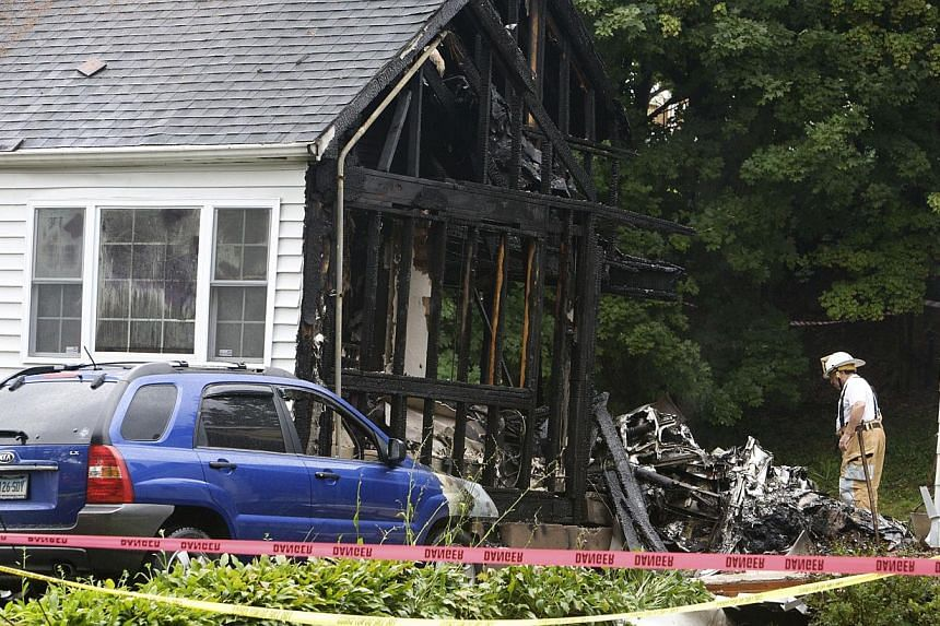 A burnt home is pictured at the site of a plane crash in East Haven, Connecticut, on Aug 9, 2013.United States rescue workers scrambled on Friday to find two children missing and feared dead after a twin-engine aircraft crashed into two houses
