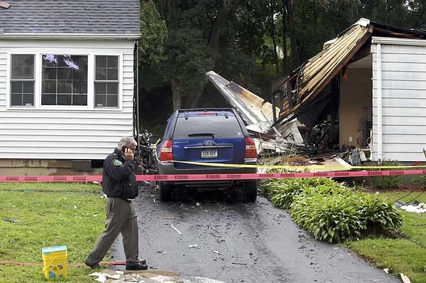 The remains of a plane is seen next to a damaged home after it crashed in East Haven, Connecticut, on Aug 9, 2013.United States rescue workers scrambled on Friday to find two children missing and feared dead after a twin-engine aircraft crashed
