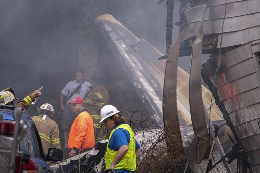 Fire and rescue personnel and residents stand near the aftermath of a plane crash between two homes in East Haven,Connecticut, on Aug 9, 2013.United States rescue workers scrambled on Friday to find two children missing and feared dead af
