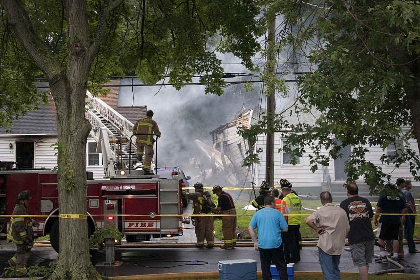 Fire and rescue personnel and residents stand near the aftermath of a plane crash between two homes in East Haven, Connecticut, on Aug 9, 2013.United States rescue workers scrambled on Friday to find two children missing and feared dead after a