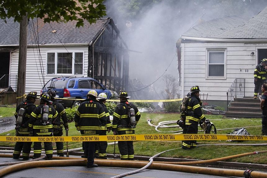Fire and rescue personnel surround the site of a plane crash in East Haven, Connecticut, on Aug 9, 2013. United States rescue workers scrambled on Friday to find two children missing and feared dead after a twin-engine aircraft crashed in
