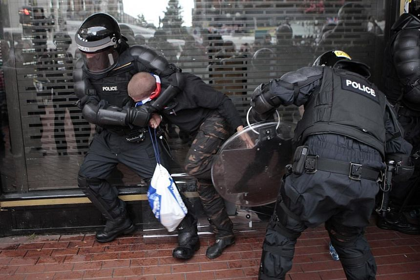 A loyalist is arrested by riot police in the centre of Belfast, Northern Ireland on Friday, Aug 9, 2013. -- PHOTO: AP