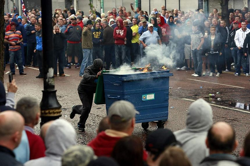 A loyalist protester pushes a garbage dumpster, that has been set alight, during clashes with the police as they wait for a republican parade to make its way through Belfast City Centre on Friday, Aug 9, 2013. -- PHOTO: REUTERS