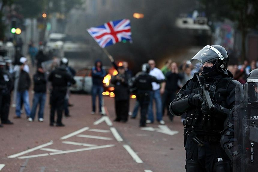 Police officers patrol the streets after loyalist protesters attacked the police with bricks and bottles as they waited for a republican parade to make its way through Belfast City Centre on Friday, Aug 9, 2013. -- PHOTO: REUTERS