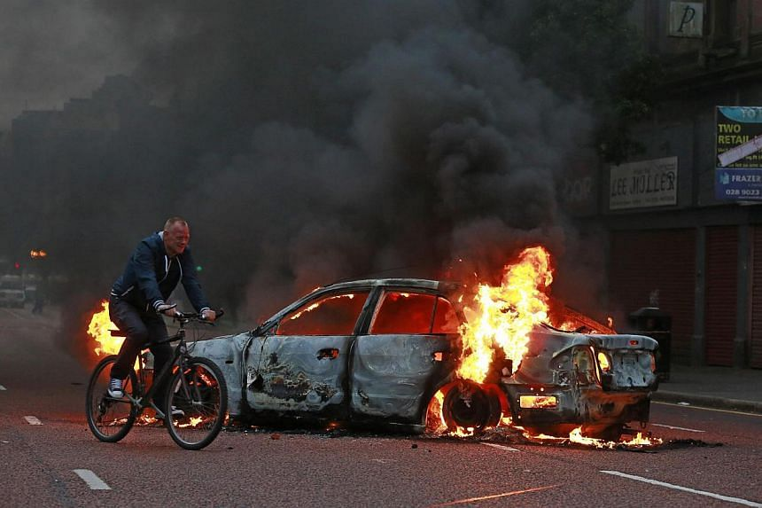 A man cycles past a burning car after loyalist protesters attacked the police with bricks and bottles as they waited for a republican parade to make it's way through Belfast City Centre on Friday, Aug 9, 2013. -- PHOTO: REUTERS