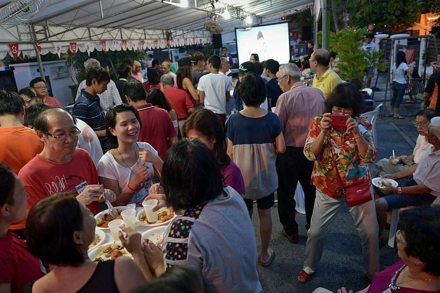 Residents of Jalan Bintang Tiga in Siglap and their neighbours tucking into food as they watched a live telecast of the NDP last night. The National Day street party there has been an annual affair for 13 years. -- ST PHOTO: NG SOR LUAN