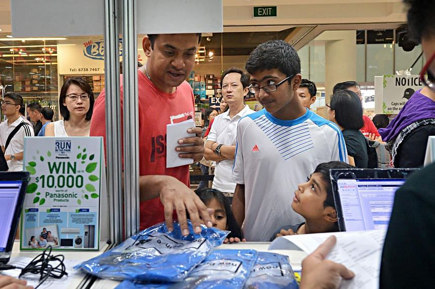 Mr Sashi collecting race packs with his 12-year-old nephew Harresh (wearing spectacles) and son Kishan Pany, seven, who are also participating in the run. -- ST PHOTOS: NURIA LING