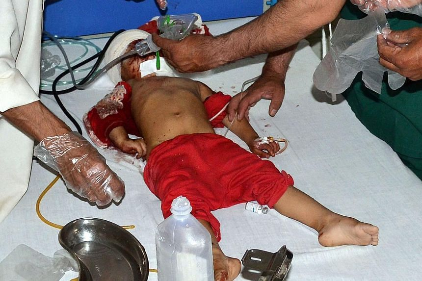 Pakistani paramedics treating an injured child at a hospital in Quetta on August 7, 2013, following a bomb explosion that killed a woman and two children as they shopped in a Pakistani market for the Muslim festival of Eid al-Fitr. The bomb exploded