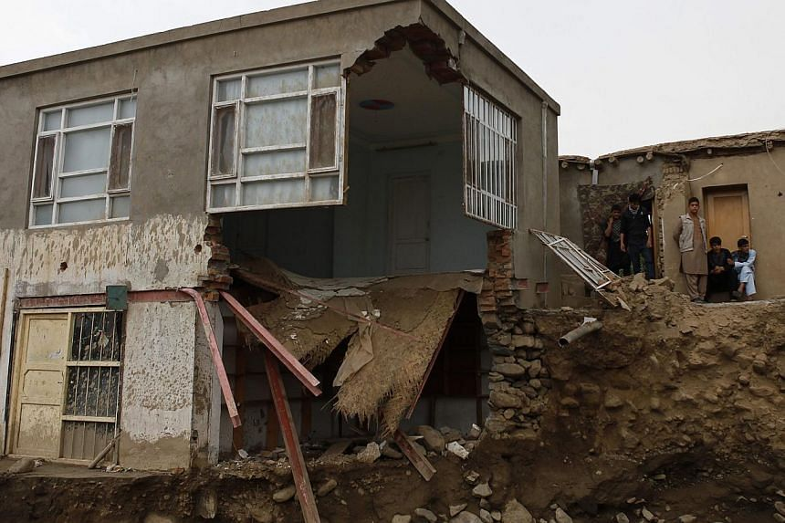 Afghans stand near a destroyed house after floods in the Shakar Dara district of Kabul on Sunday, Aug 11, 2013. Flash floods triggered by heavy rain and hail storms killed more than 20 people on the outskirts of Kabul, Afghan officials said on Sunday