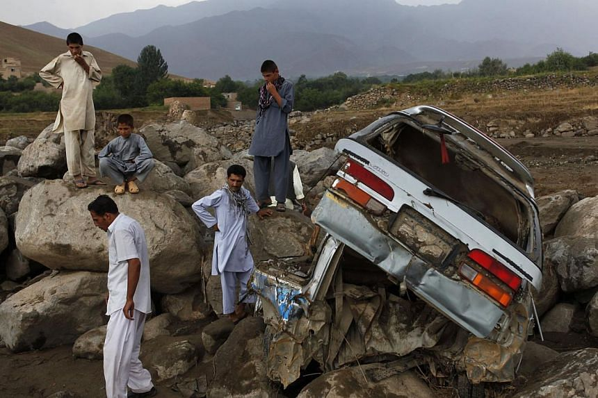 Afghans stand near a destroyed car after floods in the Shakar Dara district of Kabul on Sunday, Aug 11, 2013. Flash floods triggered by heavy rain and hail storms killed more than 20 people on the outskirts of Kabul, Afghan officials said on Sun