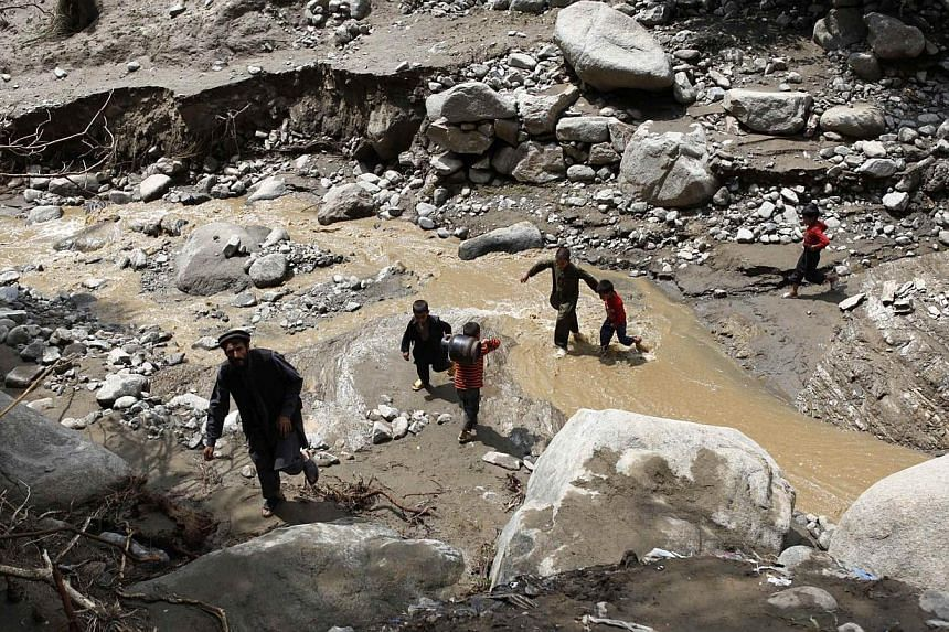 Afghan boys cross flood waters in the Shakar Dara district of Kabul on Sunday, Aug 11, 2013.Flash floods triggered by heavy rain and hail storms killed more than 20 people on the outskirts of Kabul, Afghan officials said on Sunday, with a mosqu