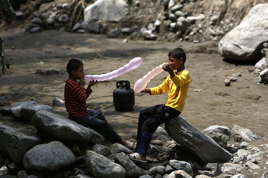 Afghan boys play with balloons near the site of floods in the Shakar Dara district of Kabul on Sunday, Aug 11, 2013. Flash floods triggered by heavy rain and hail storms killed more than 20 people on the outskirts of Kabul, Afghan officials said