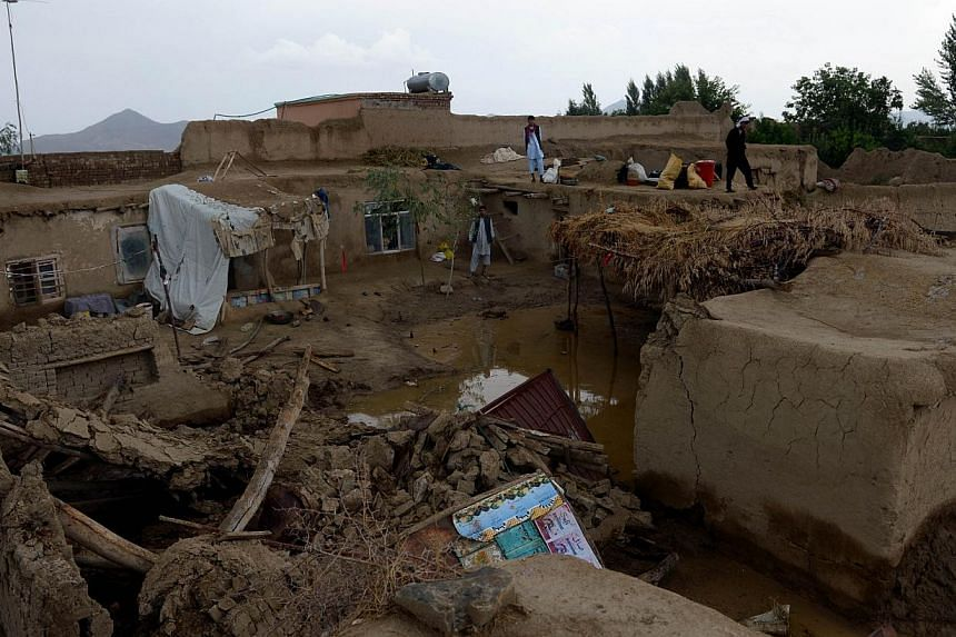 Afghans villagers look at their flood-hit homes in the Ghaaza area, in Shakardara district of Kabul province on Sunday, Aug 11, 2013. Flash floods triggered by heavy rain and hail storms killed more than 20 people on the outskirts of Kabul, Afghan of