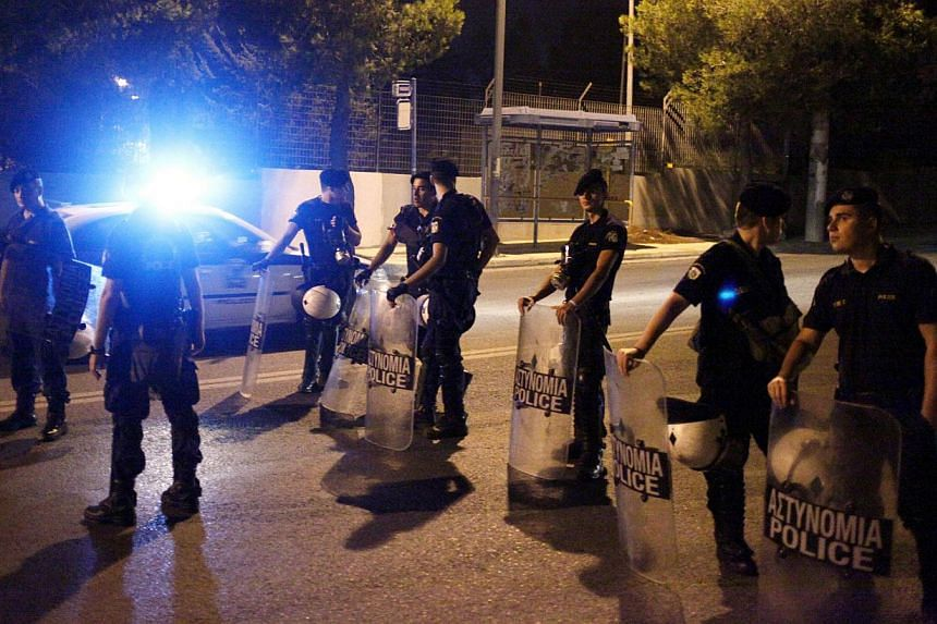 Police blocks the access to the Amygdaleza detention camp outside Athens, where some 1,200 mainly Asian migrants are kept under police guard early on Sunday, Aug 11, 2013.A police hunt for migrant escapees was under way in Athens on Sunday afte
