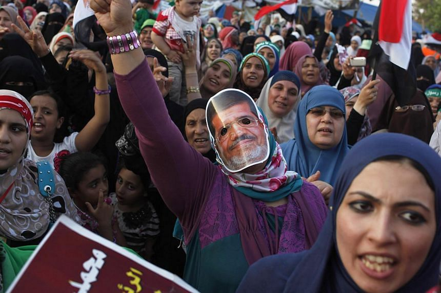 A supporter of deposed Egyptian President Mohamed Mursi, wearing a mask depicting his face, chants slogans with other protesters during a rally inside the sit-in area of Rab'a al-Adawiya Square, where they are camping, in Cairo on Aug 10, 2013. Suppo