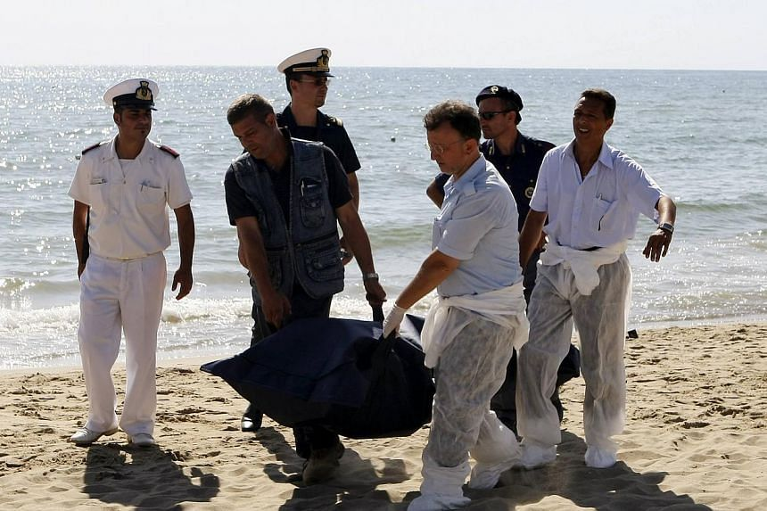 Italian police carry the body of a migrant who drowned after a shipwreck, at La Playa beach in Catania on Sicily island on Aug 10, 2013. The six migrants who drowned off a tourist beach in Sicily, after their boat was abandoned at sea by a larger ves