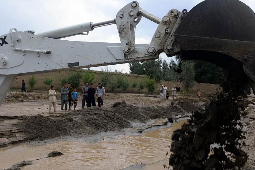 Afghan villagers look on as a excavator diverts the water path in the flood-hit Ghaaza area, in Shakardara district of Kabul province on Sunday, Aug 11, 2013.Flash floods triggered by heavy rain and hail storms killed more than 20 people on the