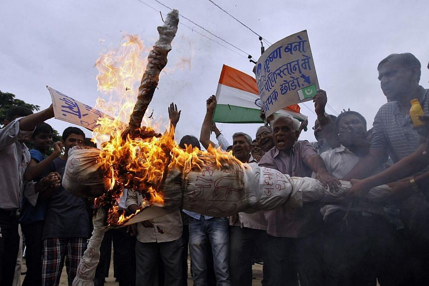 Protesters burn an effigy depicting Pakistan's Prime Minister Nawaz Sharif during a protest against Pakistan in the western Indian city of Ahmedabad on Aug 10, 2013. India and Pakistan exchanged more gunfire across the disputed border in Kashmir on S