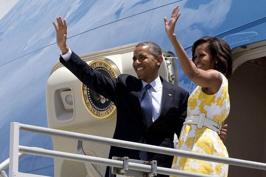 President Barack Obama and first lady Michelle Obama wave goodbye as they leave Orlando, Florida, Saturday, Aug 10, 2013, en route to Martha's Vineyard, Massachusetts, for a family vacation. -- PHOTO: AP