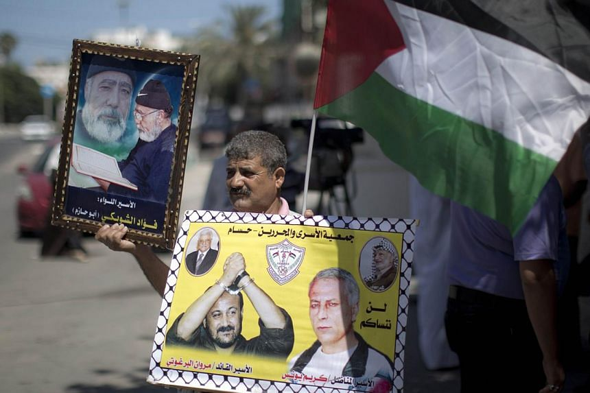 A Palestinian man holds placards featuring Palestinian prisoners during a protest to demand the release of Palestinian prisoners held in Israeli jails on July 29, 2013 in Gaza city.Israel on Monday published a list of 26 Palestinian priso