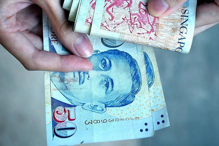 A woman holds a stack of $50 Singapore dollars. The Singapore dollar turned lower on Monday as investors took profits after the currency rose to a near eight-week top, while the Malaysian ringgit gained on catch-up buying after holidays. -- NP FILE P
