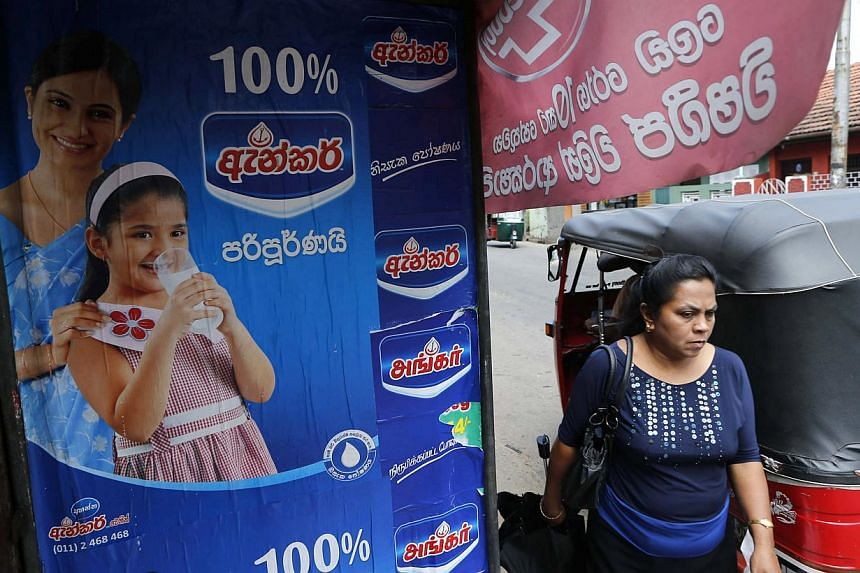 A Sri Lankan woman walks past an advertisement of a Fonterra product in Colombo, Sri Lanka, on Tuesday, Aug 6, 2013. New Zealand on Monday rejected allegations from Sri Lanka that its dairy products were contaminated with a farm chemical, accusing in