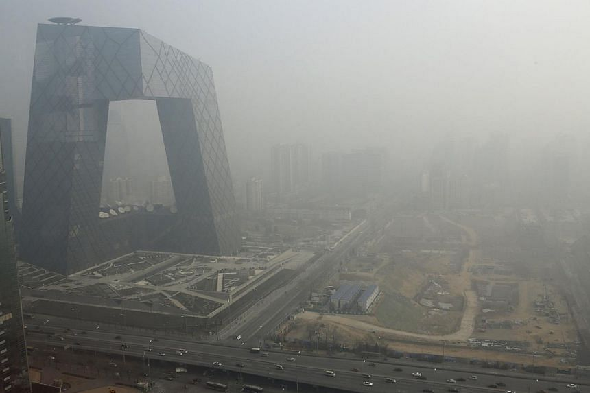 The China Central Television (CCTV) building is seen next to a construction site in heavy haze in Beijing's central business district in this Jan 14, 2013 file photo. China plans to accelerate investment in technology to save energy and tackle the di