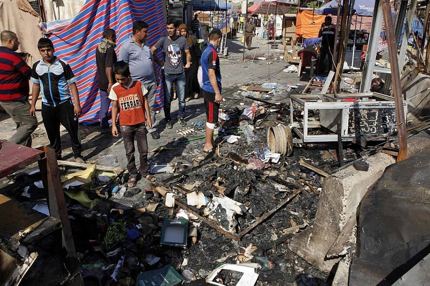 People inspect the aftermath of a car bomb attack on a store in the New Baghdad neighborhood of Baghdad, Iraq, on Sunday, Aug 11, 2013. An Al-Qaeda front group on Sunday claimed a wave of attacks that killed dozens of people during the Eid al-Fitr ho