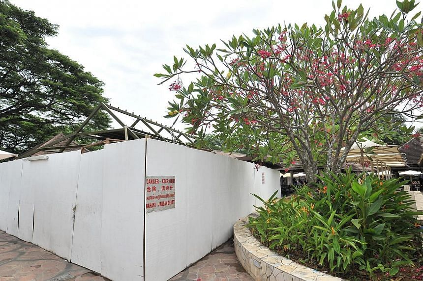 The four stalls that were badly damaged in a fire that happened on June 28 2013, are surrounded by white boards with danger signs at East Coast Lagoon Food Village on Aug 11 2013. -- PHOTOS: LIM YAOHUI FOR THE STRAITS TIMES